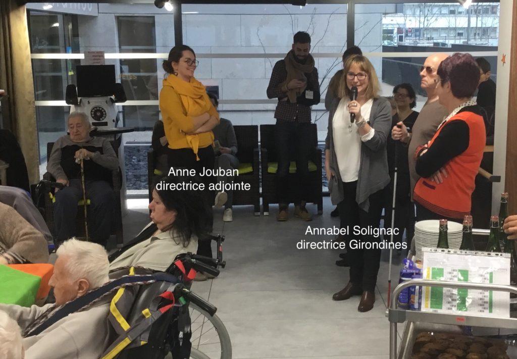 vœux de la ville de Lyon pour 2018 - Annabel Solignac au micro, Anne Jouban debout face à elle et quelques résidents.